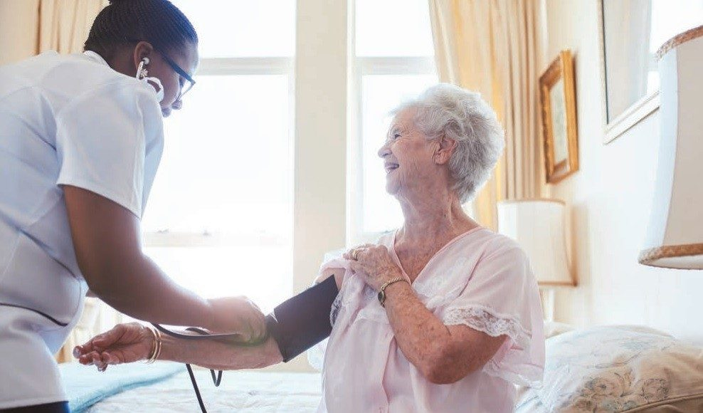 Care home resident having blood pressure checked